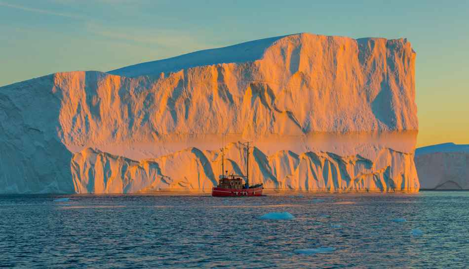 Tourists take pictures of the iceberg. Source of icebergs is by the Jakobshavn glacier. This is a consequence of the phenomenon of global warming and catastrophic thawing of ice, Disko Bay, Greenland