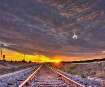 Sunset rays streak from below the cirrocumulus clouds over train