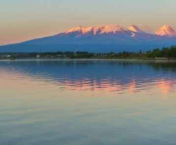 Sunset lighting Kluchevskaya group of volcanoes with reflection in river