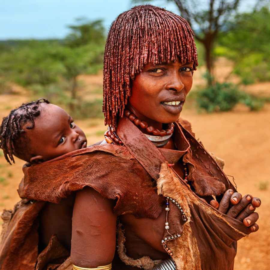 Woman from Hamer tribe carrying her baby, Ethiopia, Africa